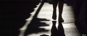 person's dark shadow on road surface in town